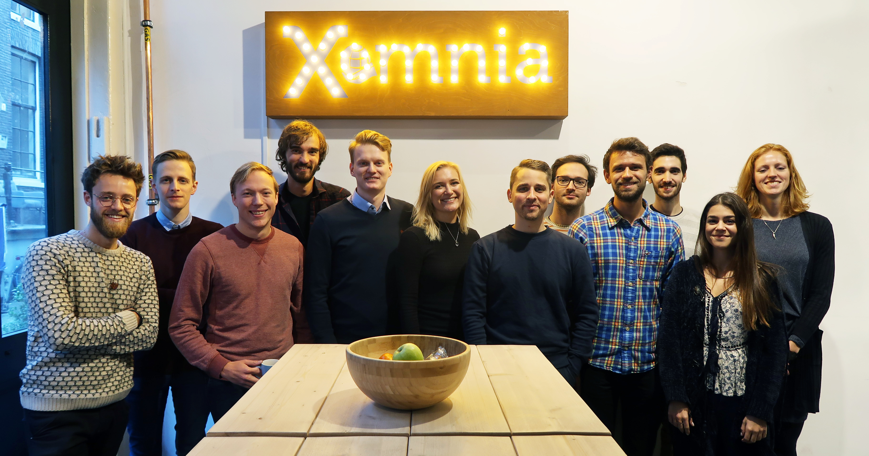 group of junior data science and data engineers from Xomnia junior development programme. Group is standing in front of the Xomnia sign.
